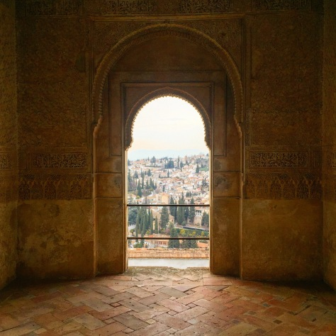 A typical Moorish arch overlooking overlooking the terracotta roofs of Granada far below.